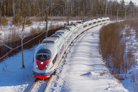 Foto per Fryazevo, Moscow region, Russia - March 08, 2018: Modern high-speed train moves fast at winter morning time. Train driver greets photographer. - Immagine Royalty Free