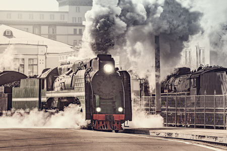Foto de Retro steam train departs from the railway station. - Imagen libre de derechos