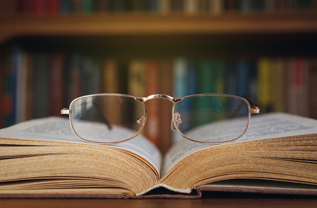 Photo pour glasses and book on background bookcase - image libre de droit
