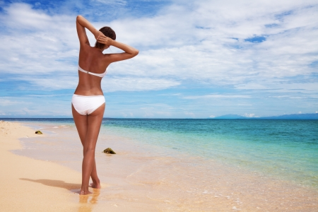 Tanned woman's back relaxing on the sandy beach