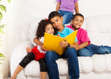 Family, group of four kids with older brother reading books to brothers and sister hugging little girl