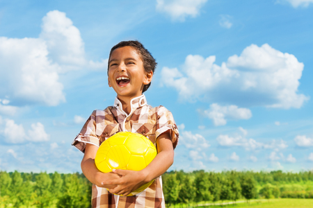 Laughing dark boy holding yellow volley ball standing in the park on sunny day with blue clouds