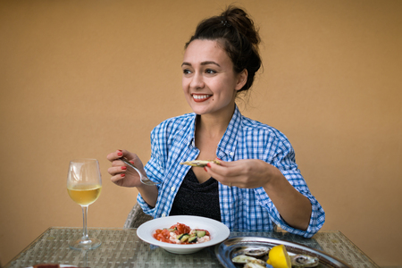 Photo for Young happy woman sits at the table with local food and glass of sparkling wine. Beautiful girl ready to eat and holds in hands oyster and fork on the background of yellow wall - Royalty Free Image