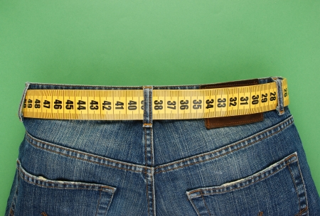 Foto de jeans with meter belt slimming on the green background - Imagen libre de derechos