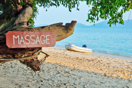 Foto de Old signboard with the inscription, massage, on a tropical beach - Imagen libre de derechos
