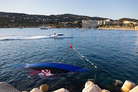 Photo for Shipwrecked half-submerged yacht in the calm waters of the Bay of Mallorca - Royalty Free Image