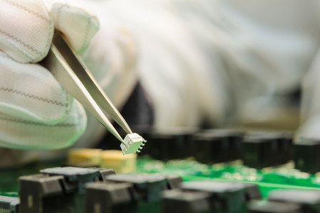 Photo pour Female hand in ESD gloves holding tweezers and assembling white microchip on printed circuit board - image libre de droit