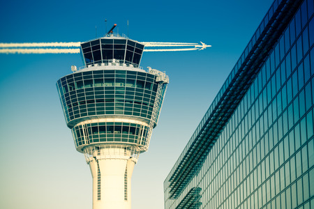 Foto de Flights management air control tower and passenger terminal in Munich international airport with flying plane in clear sky. Stock photo with split toning effect. - Imagen libre de derechos