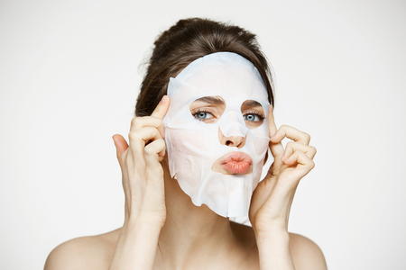 Photo pour Young girl with facial mask looking at camera over white background. Cosmetic procedure. Beauty spa and cosmetology. - image libre de droit