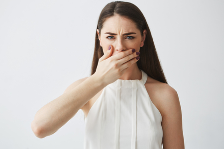 Foto de Displeased young brunette girl covering mouth with hand looking at camera over white backround. - Imagen libre de derechos