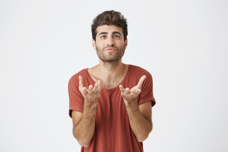 Photo for Studio portrait of attractive bearded student in red t-shirt stretching his hands to the camera. Emotional man with stylish hairstyle not understanding what is wanted from him - Royalty Free Image