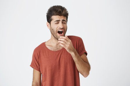 Photo for Yawning young fellow with beard and trendy hairstyle tired of work and holding his hand behind his mouth. Student wearing red T-shirt got bored of lectures - Royalty Free Image