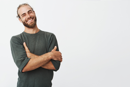 Photo for Attractive swedish man with stylish hair and beard laughs at funny story from friend with crossed hands and closed eyes. - Royalty Free Image