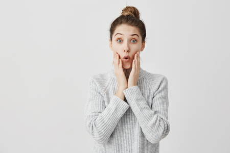 Photo for Young woman making surprise with facial expressions and touching her cheeks. Girl in fashion being excited to know interesting gossip goggle at talker. Human emotions - Royalty Free Image