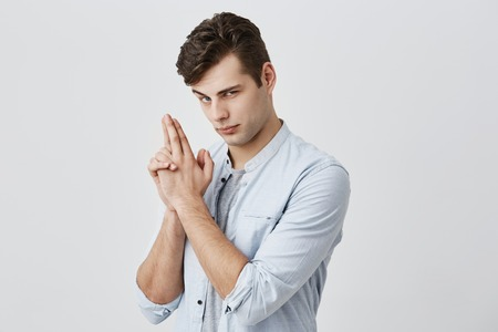 Photo pour Positive having fun caucasian male with dark hair and blue eyes, raised hie eyebrow, making faces, seriously looking at camera, gesturing pretending to have gun. Fun and youth concept - image libre de droit