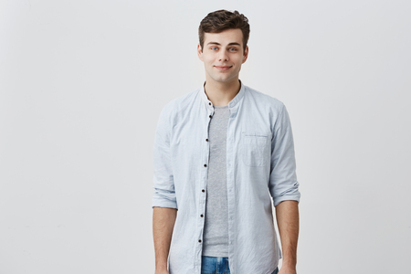 Foto de Cheerful pleased caucasian guy with blue eyes and dark hair dressed in elegant blue shirt smiling in good mood while posing in studio against gray background. Facial expressions concept - Imagen libre de derechos