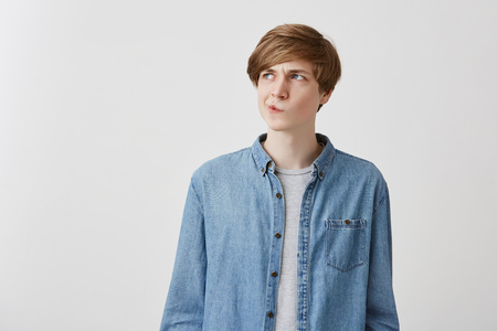 Foto de I dont know. Doubtful caucasian young male wearing denim shirt, pouting lips and looking up with indecisive expression on his face, showing doubt and hesitation. Body language and face expression - Imagen libre de derechos