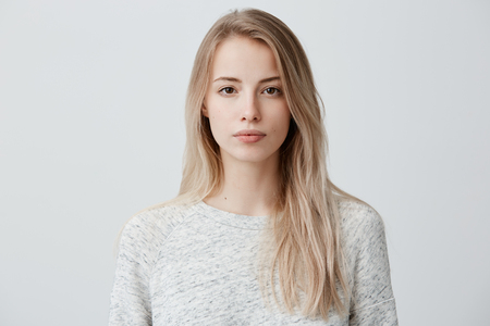Photo for Confident good-looking beautiful woman with blonde dyed hair with healthy pure skin dressed in casual clothes looking seriously at camera. Youth and beauty concept - Royalty Free Image