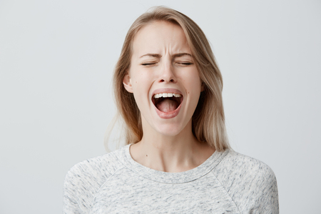 Photo for Emotional blonde woman opening her mouth widely screaming loudly being dissatisfied with something expressing disagreement and annoyance. Female shouting at boyfriend, Negative emotions and feelings - Royalty Free Image