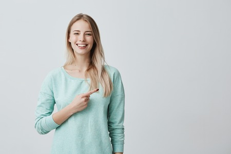 Foto de Advertising concept. Smiling cheerful positive european woman wearing light blue shirt pointing her index finger aside at copy space for promotional text, motivating and attracting customers. - Imagen libre de derechos