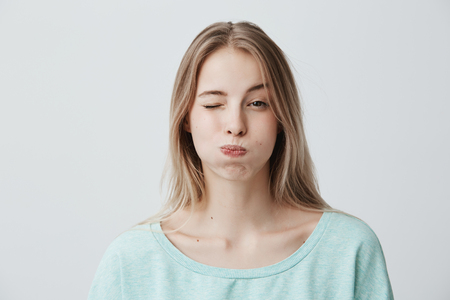 Foto de Portrait of frowning blonde young woman dressed in light blue sweater, pouting her cheeks, blinking, doesn`t want to share information. Human emotions, face expression, reaction and attitute - Imagen libre de derechos