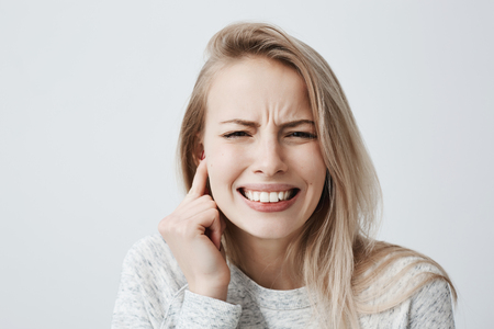 Photo pour Horizontal portrait of blonde caucasian female dressed casually has headache after noisy party, clenches teeth and holds hand behind her ear. Irritated young female expressing negative emotions. - image libre de droit