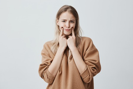 Photo pour Studio shot of beautiful blonde woman making grimace, touching her cheeks with fingers, making herself smile, frowning face, being displeased and upset. Face expression and negative emotions - image libre de droit