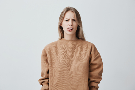 Photo pour Naughty beautiful girl with blonde long hair in beige sweater misbehaving, sticking out tongue at camera as a sign of disobedience, protest and disrespect. Emotions, reaction, feelings and attitude - image libre de droit