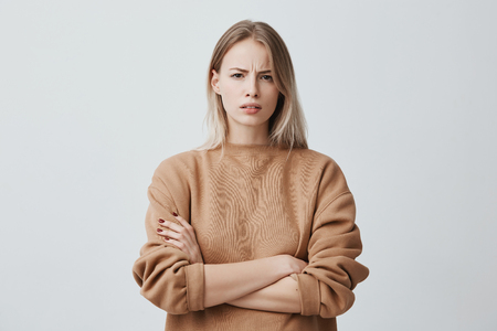 Foto de Waist-up portrait of beautiful girl with blonde straight hair frowning her face in displeasure, wearing loose long-sleeved sweater, keeping arms folded. Attractive young woman in closed posture. - Imagen libre de derechos