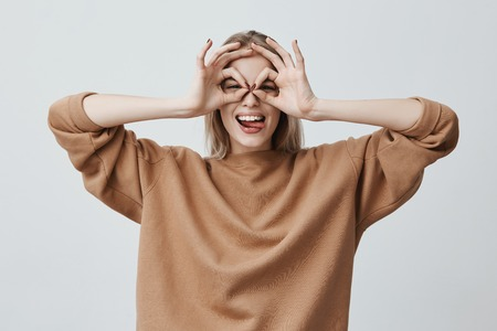 Photo pour Cheerful excited female with blonde long straight hair showing Ok gestures with both hands, pretending to wear spectacles, and smiling broadly, enjoying her carefree happy life - image libre de droit