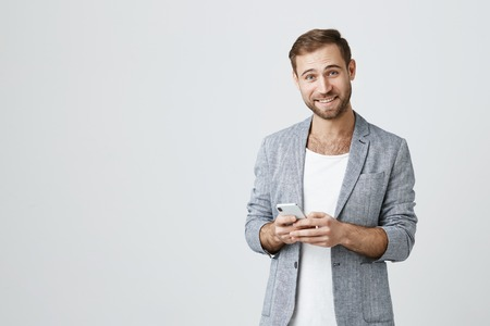 Foto de Joyful Caucasian handsome man with stubble dressed stylishly using mobile phone, surfing internet. Happy smiling guy in stylish clothes using wifi on cell phone - Imagen libre de derechos