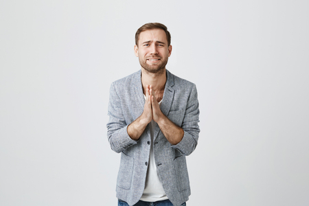 Foto de Isolated shot of bearded handsome male wears fashionable clothes, keeps palms together as prays for good luck, has sad unhappy expression, isolated against gray background. Facial expression - Imagen libre de derechos