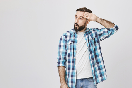 Photo pour Adult bearded guy wiping his forehead with hand making phew gesture, expressing relief while standing against gray wall. Man feels happy that he prevented huge disaster. It was close enough - image libre de droit