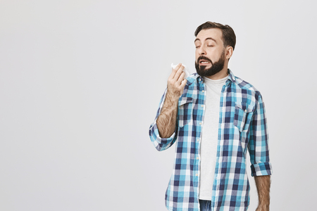 Photo pour Studio shot of sick man who is about to sneeze with closed eyes and opened mouth while holding napkin in hand, standing over gray background. Friend has cat and this guy is allegic to it. - image libre de droit