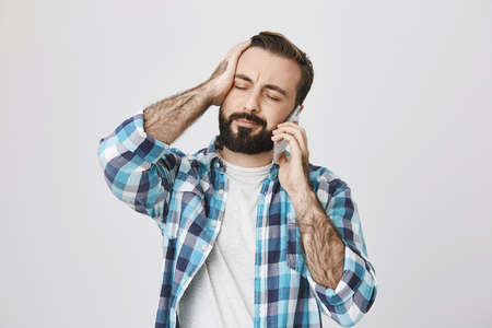 Photo for Portrait of tired and perplexed young adult with beard and moustache closing eyes and holding hand on head while talking on smartphone, over gray background. Worker forgot about his shift - Royalty Free Image