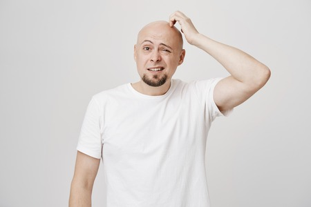 Photo for Portrait of confused bald caucasian male model with stupid expression, scratching head and looking aside not having any clue, standing over gray background. Man forgot something but do not know what - Royalty Free Image