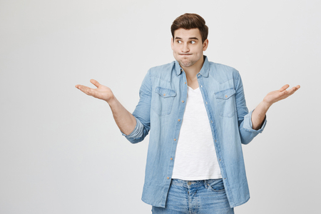 Photo for Portrait of funny handsome guy, shrugging and spreading hands, expressing unknowladge and confusion, widen eyes, standing over gray background. I do not know what are you talking about - Royalty Free Image