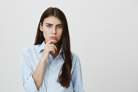 Foto de Indoor portrait of attractive european model holding hand near chin staring at camera with frowned eyebrows and serious face, expressing disbelief over gray background. Girl thinks boyfriend lies - Imagen libre de derechos