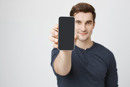 Foto de Portrait of young european model advertising new smartphone, showing it to camera, standing over gray background. Shop assistant shows new device that arrived to store, explaining facilities - Imagen libre de derechos