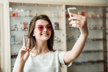 Photo pour Good-looking feminine european woman in optician store taking selfie while trying on stylish sunglasses showing peace or victory sign and smiling at camera, being satisfied with purchase - image libre de droit