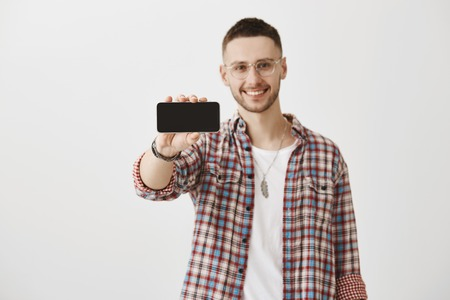Photo for Eager to buy new gadgets. Studio shot of attractive macho model in glasses pulling hand with smartphone towards camera while presenting it, smiling broadly and standing over gray background. - Royalty Free Image