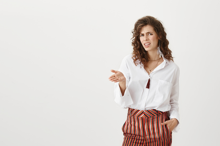 Photo for Who does he think he is. Stylish influential woman in trendy clothes gesturing and frowning, being disappointed and expressing dislike or disrespect. Boss is unsatisfied with project her employee made - Royalty Free Image