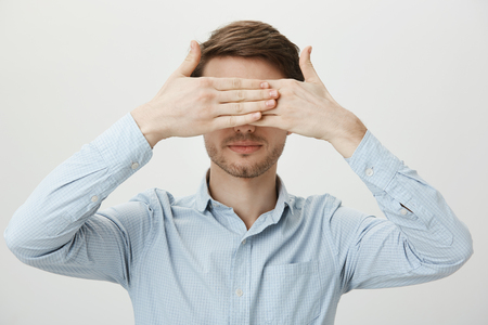 Photo for Did not see so did not happen. Portrait of calm relaxed young man with bristle covering eyes with both palms, standing in ordinary blue shirt against gray background without any emotions - Royalty Free Image
