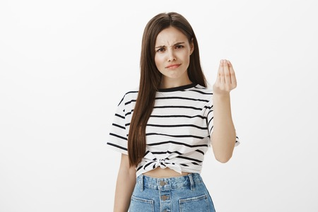 Photo for Girl wants tiny act of respect. Unsatisfied questioned european woman with brown hair, frowning from disappointment, raising hand and showing italian gesture what do you want over white wall - Royalty Free Image