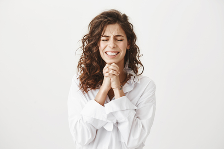 Photo pour Studio shot of worried and upset caucasian woman holding hands in pray near chin, squeezing it tight and begging for something, smiling nervously and standing with closed eyes over gray background - image libre de droit