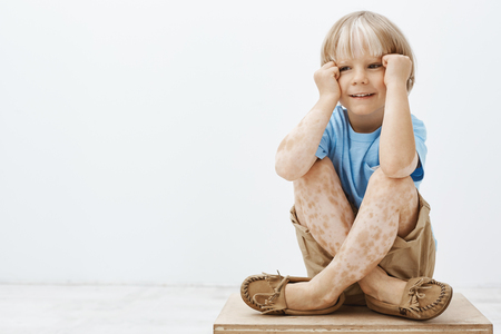 Foto de Cute little boy with blond hair and spots on skin, sitting with crossed feet, holding hands near face and smiling with joyful carefree expression, looking aside, feeling happy over grey wall - Imagen libre de derechos