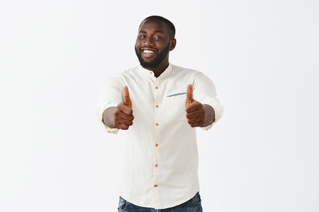 Photo for Studio shot of pleased good-looking crafty male african american chef in white shirt, smiling broadly from satisfaction, showing thumbs up at camera, liking new meal and suggesting everyone try it - Royalty Free Image