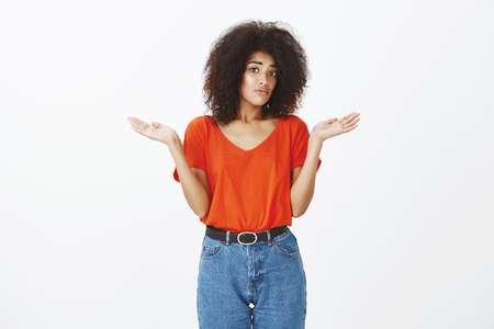 Photo pour Do not look at me, not my fault. Portrait of anxious unaware good-looking african american woman with curly hairstyle, shrugging and staring with gloomy expression at camera, being clueless - image libre de droit