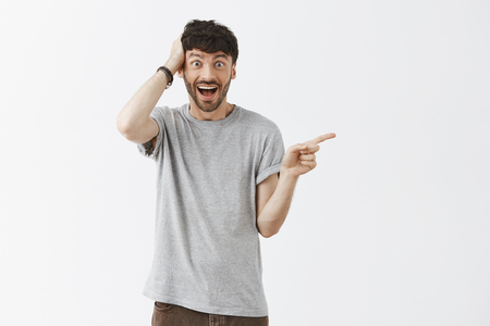 Foto de No way it cannot be true. Portrait of amazed and thrilled happy and excited good-looking young artistic guy in grey t-shirt holding hand on head and pointing right over gray background - Imagen libre de derechos