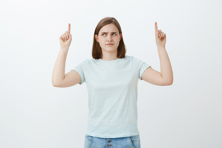 Foto de Girl have doubts think product is lame. Intense displeased cute girl with big ear frowning looking and pointing up with dislike and doubt hesitating if choice is right posing over white background - Imagen libre de derechos
